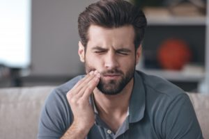 Man touching his jaw and wondering what causes toothaches
