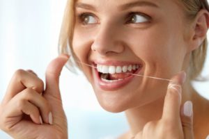 Healthy, smiling woman flossing her teeth