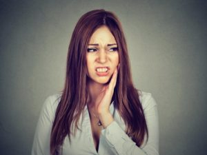 Woman holding hand to her face thinking about dental emergencies