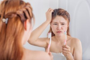 Woman with toothbrush concerned about overbrushing