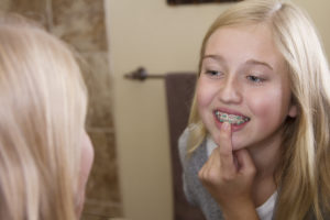 girl looking at braces in mirror